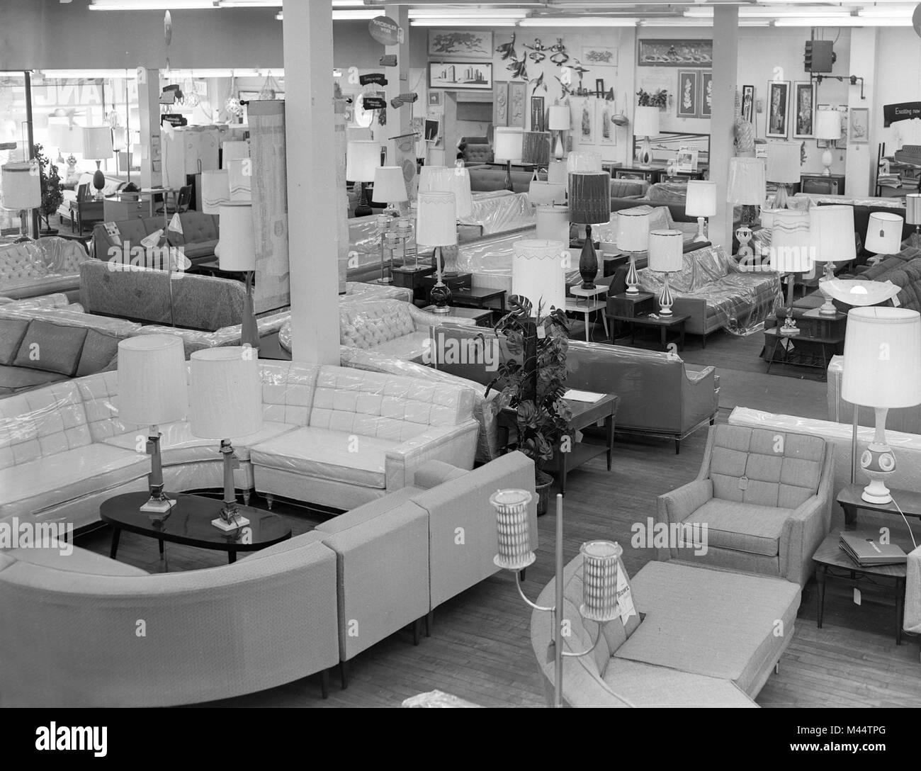 Furniture store in Chicago is crowded with sofas and lamps for mid-century homebuyers, ca. 1956. - Stock Image