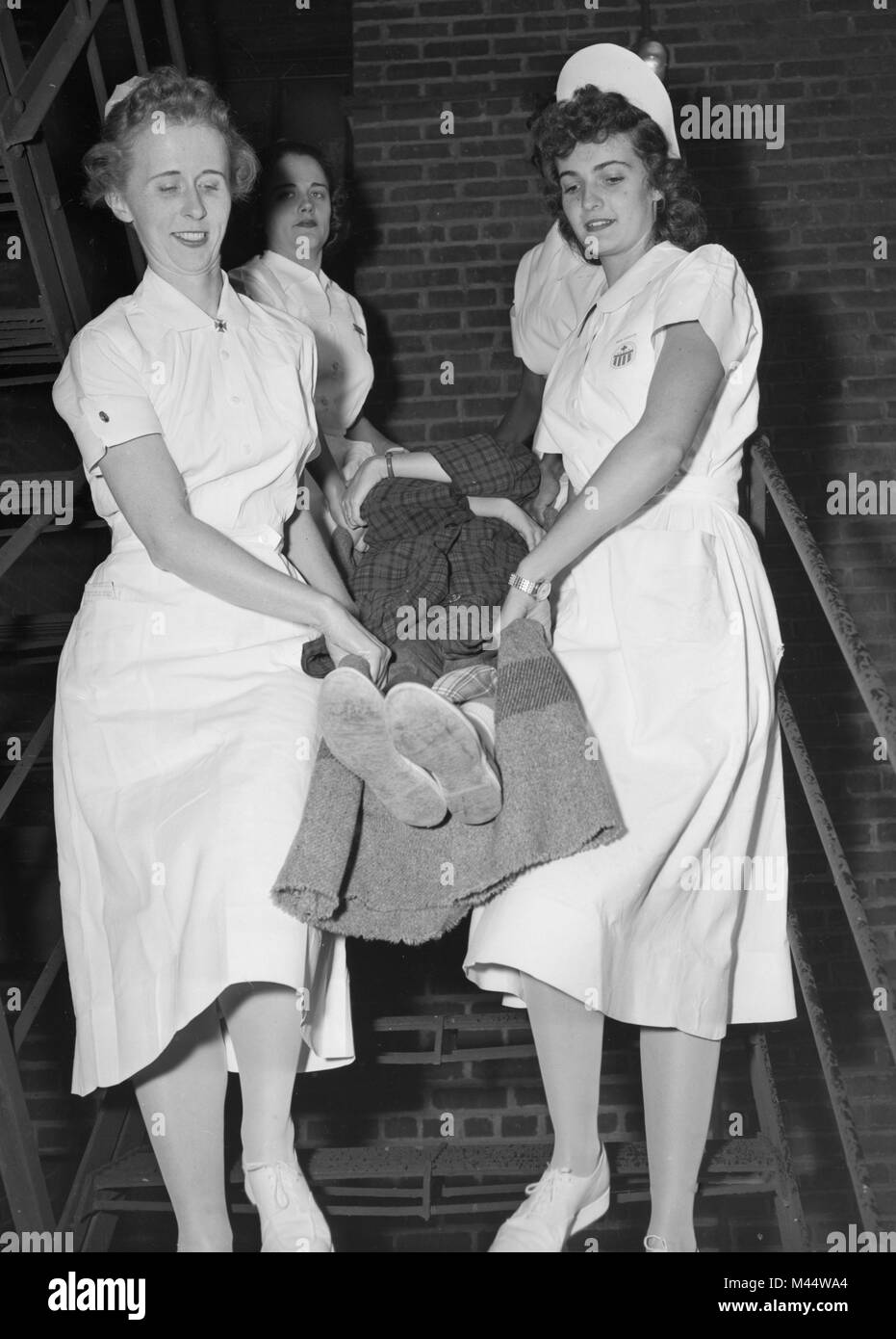 Nurses scramble down a fire escape with a patient during a mock fire drill, ca. 1958. Stock Photo