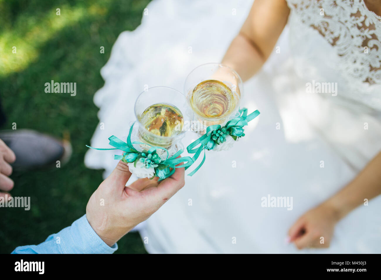 Newlyweds clink glasses with champagne on the grass - Stock Image