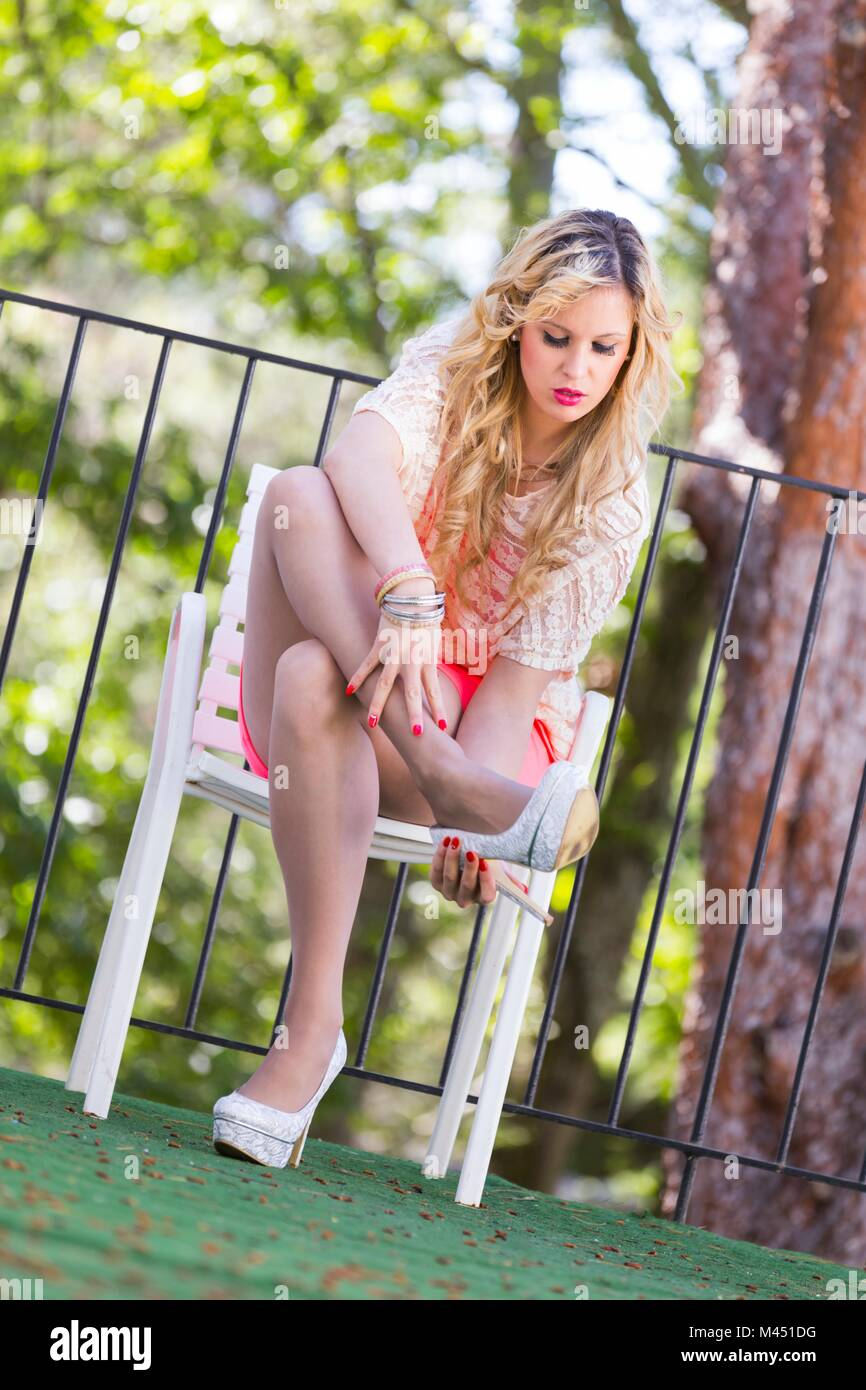 Young woman crossed legs cross legged short dress fanciful nylon tights pantyhose high-heels - Stock Image