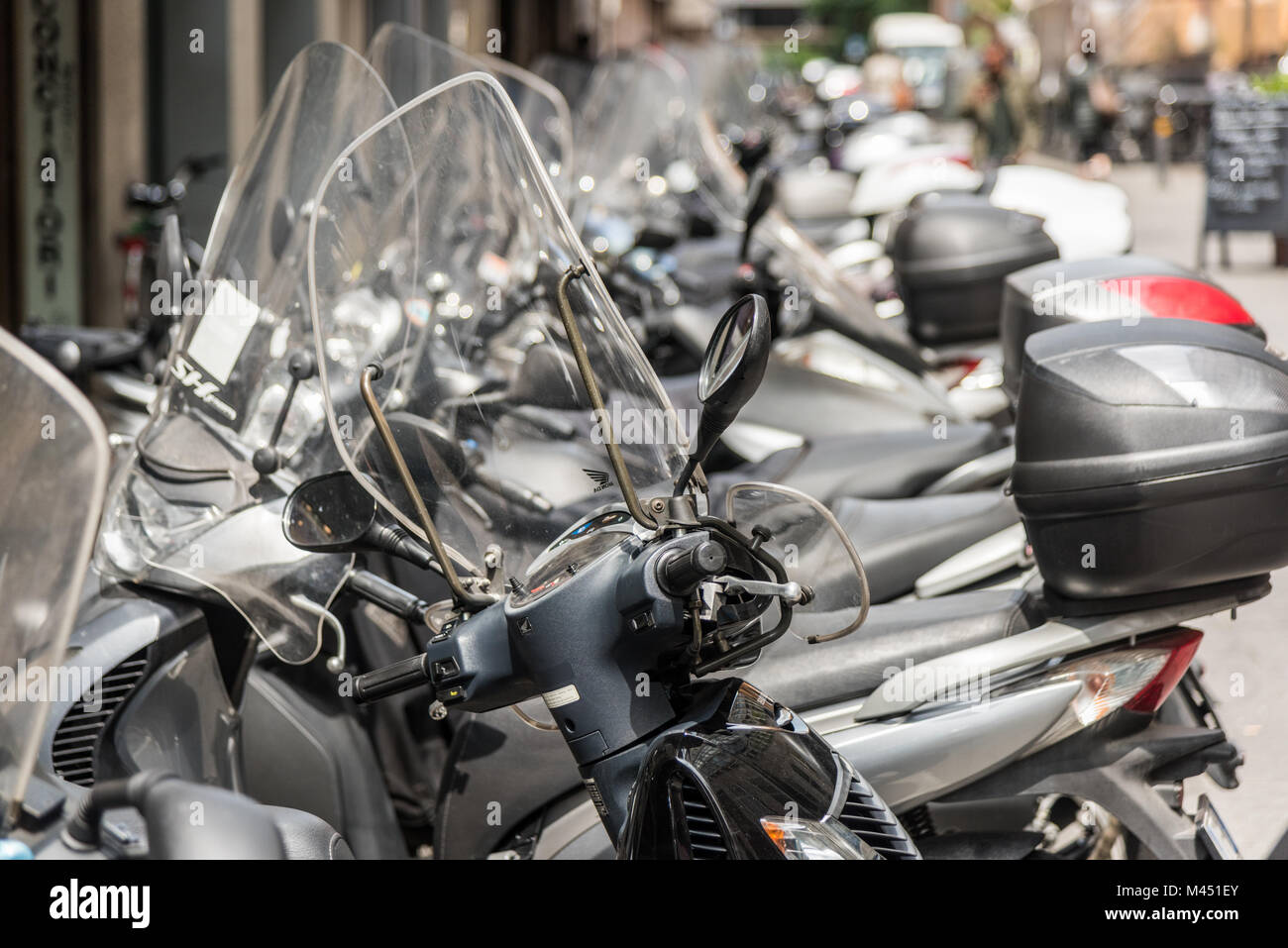 Rows of parked motorbikes and scooters in a street in the city of Bologna Italy - Stock Image