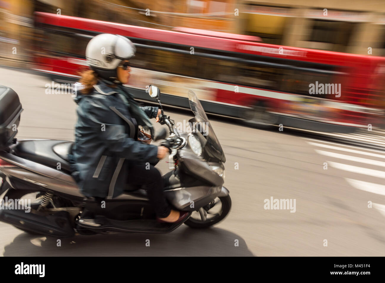 A motion blurred image of a woman on a motor scooter or motor bike in a street on the city of Bologna Italy giving - Stock Image