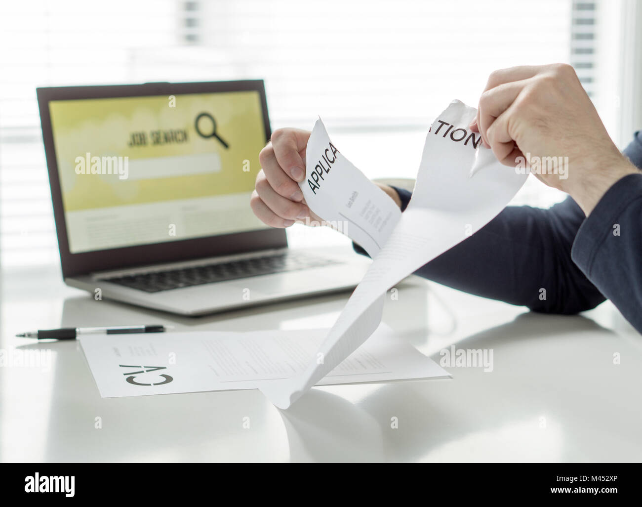 Man ripping job application paper. Person having problems writing his CV or finding work. Angry, frustrated and - Stock Image