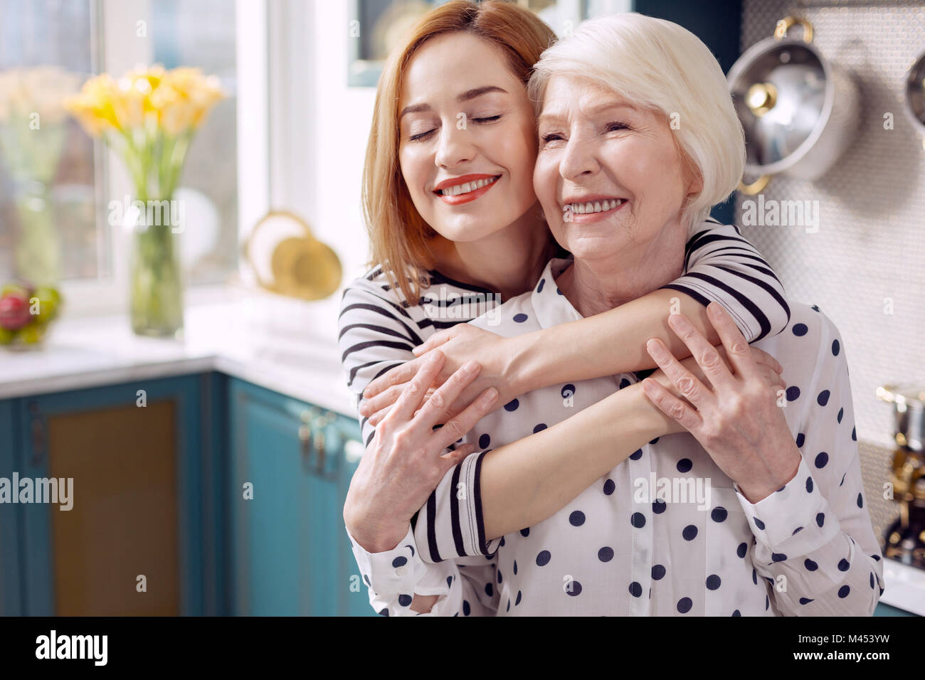 Loving daughter giving her senior mother back hug - Stock Image