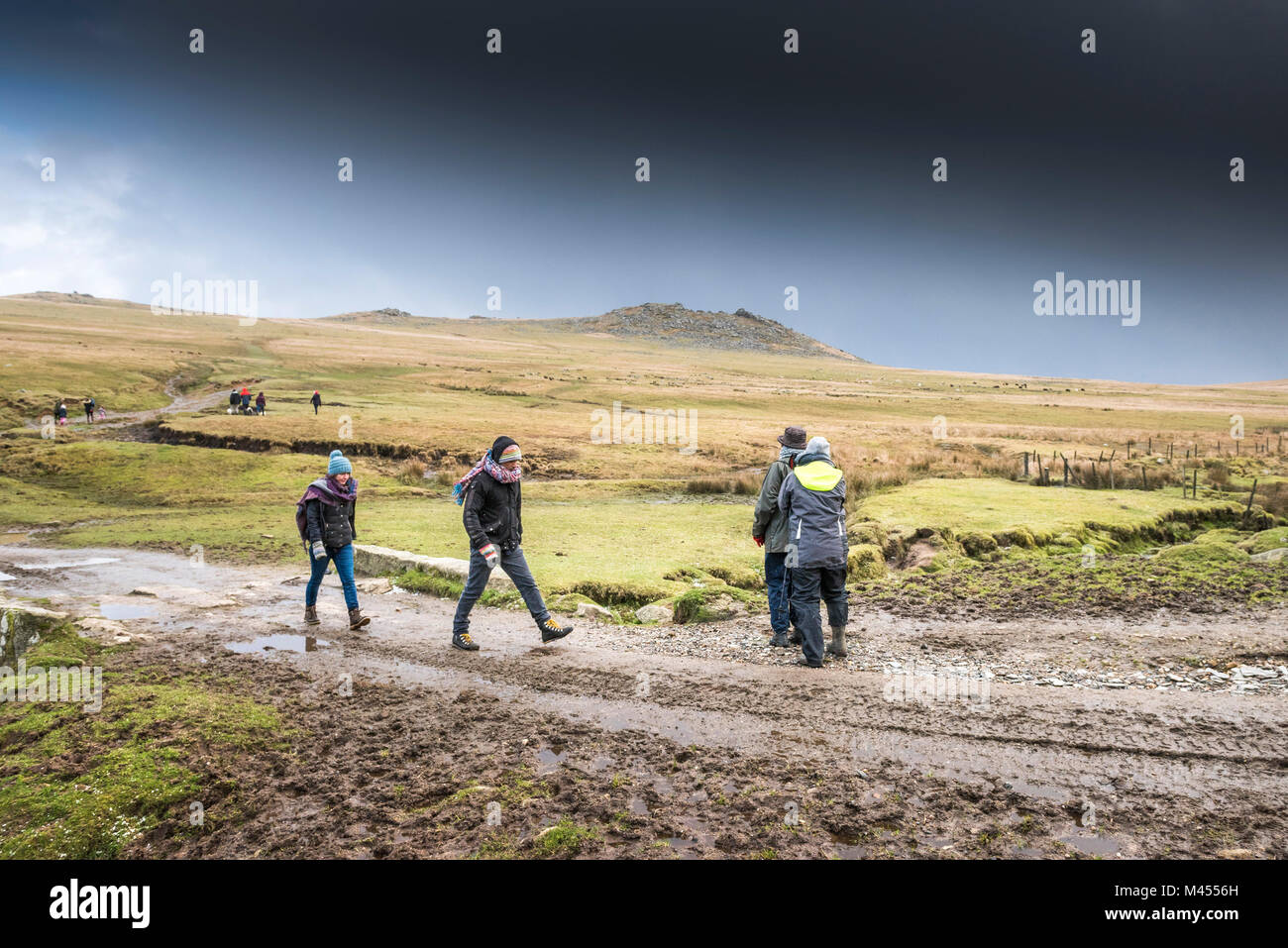 Walkers on a muddy track at Rough Tor on Bodmin Moor in Cornwall. - Stock Image