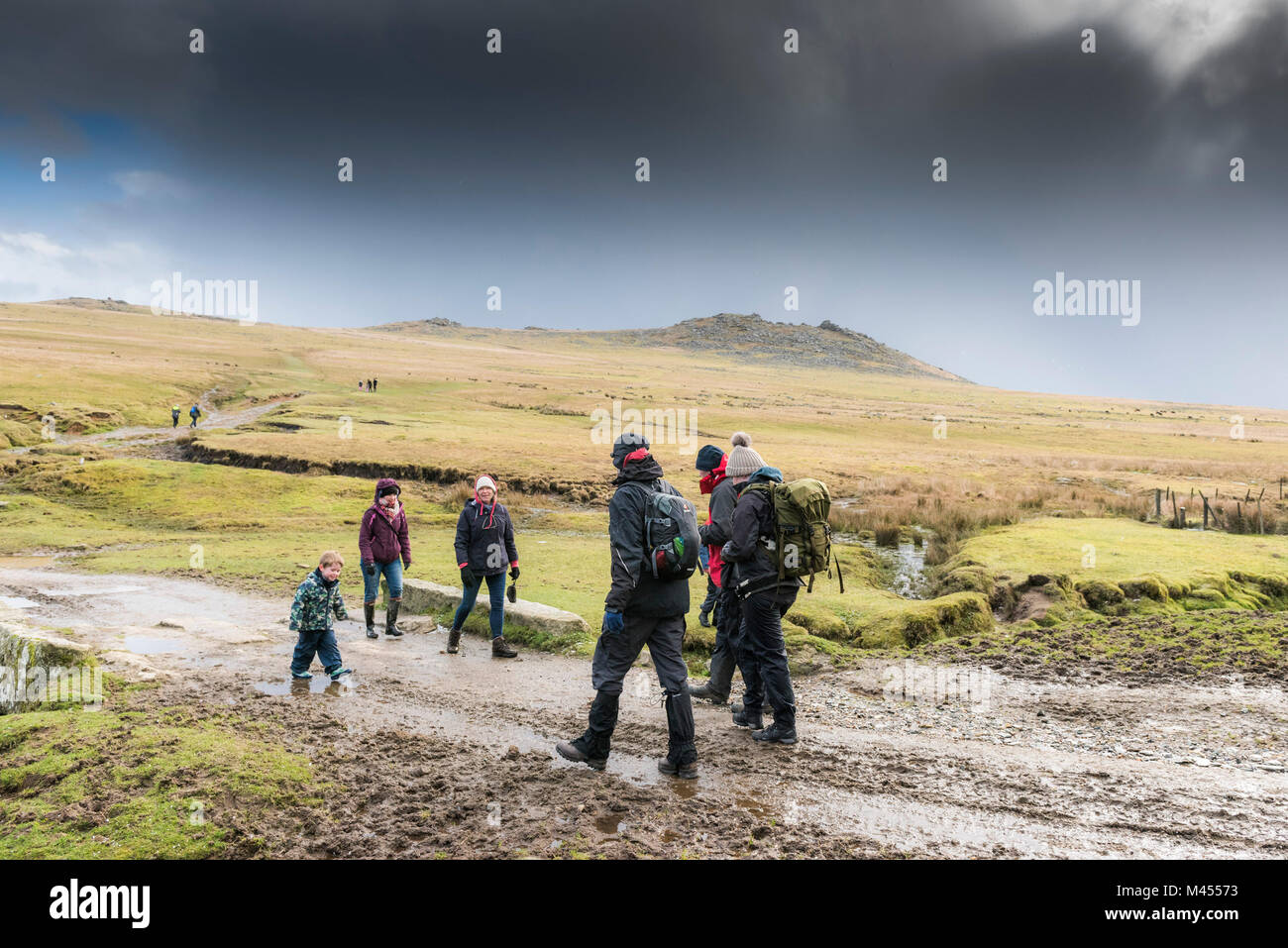 Walkers at Rough Tor on Bodmin Moor in Cornwall. - Stock Image