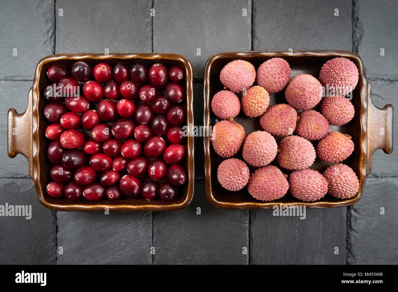 Cranberries next to lychee fruits - two square, symmetrically arranged fruit bowls - Stock Image