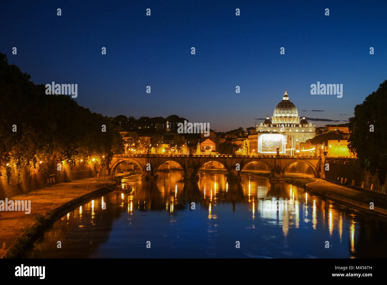 Night view of St. Peter's Basilica. Ponte Sant Angelo and Tiber River in Rome - Italy. Dramatic sunset with - Stock Image