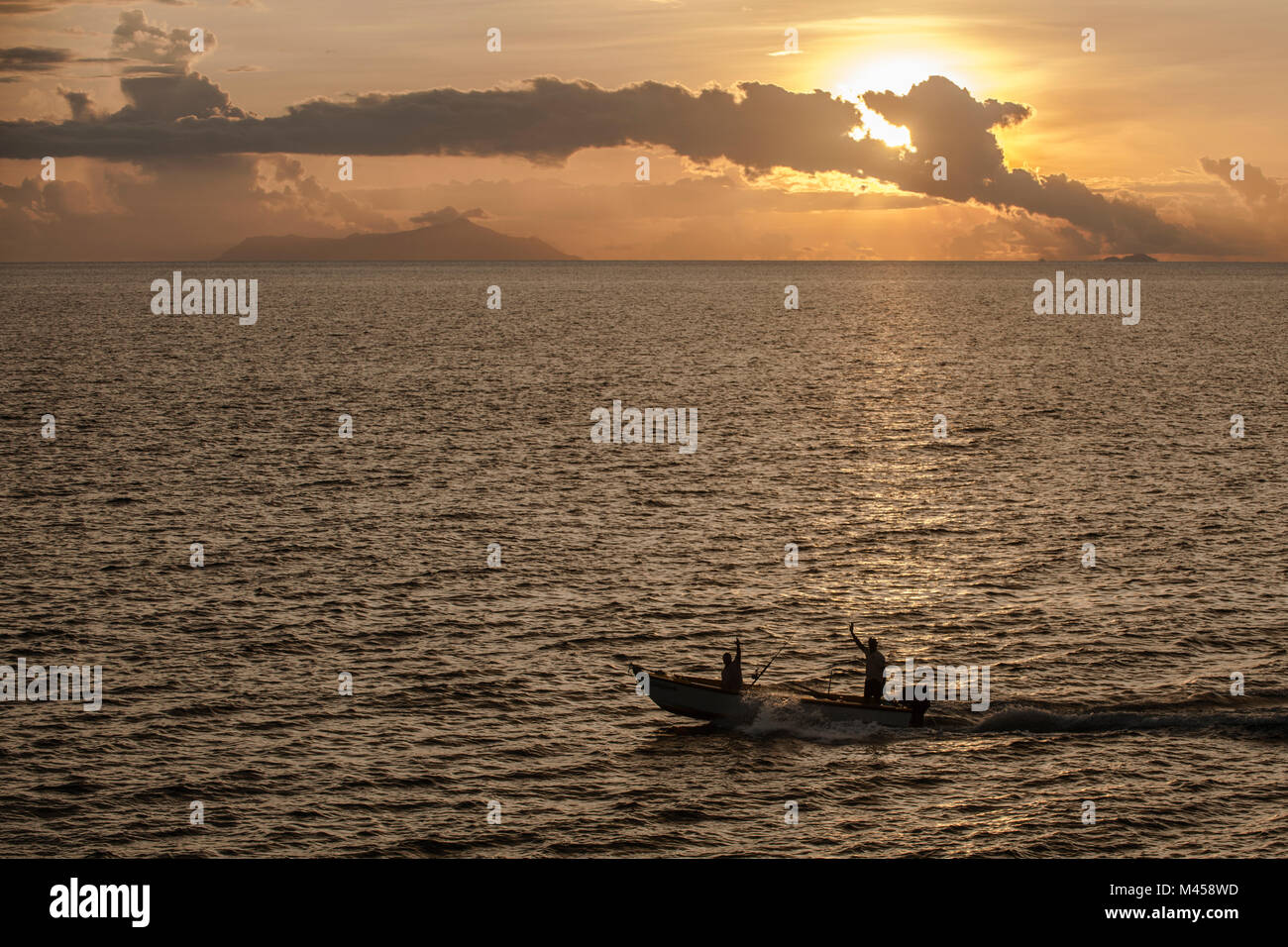 Fisherman wave as they pass on their boat Praslin, the Seychelles.  Credit: Euan Cherry - Stock Image