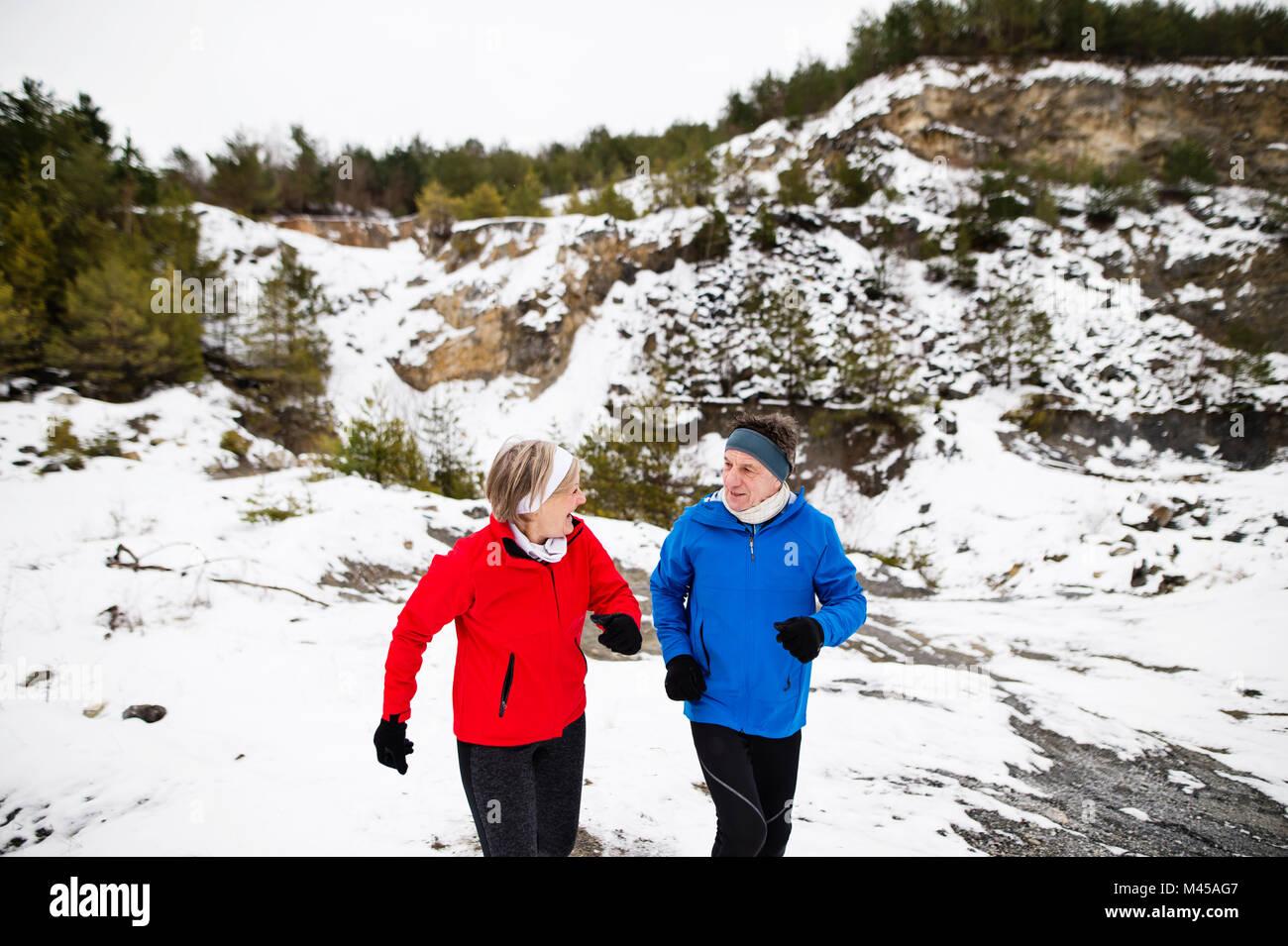 Senior couple jogging in winter nature. Stock Photo