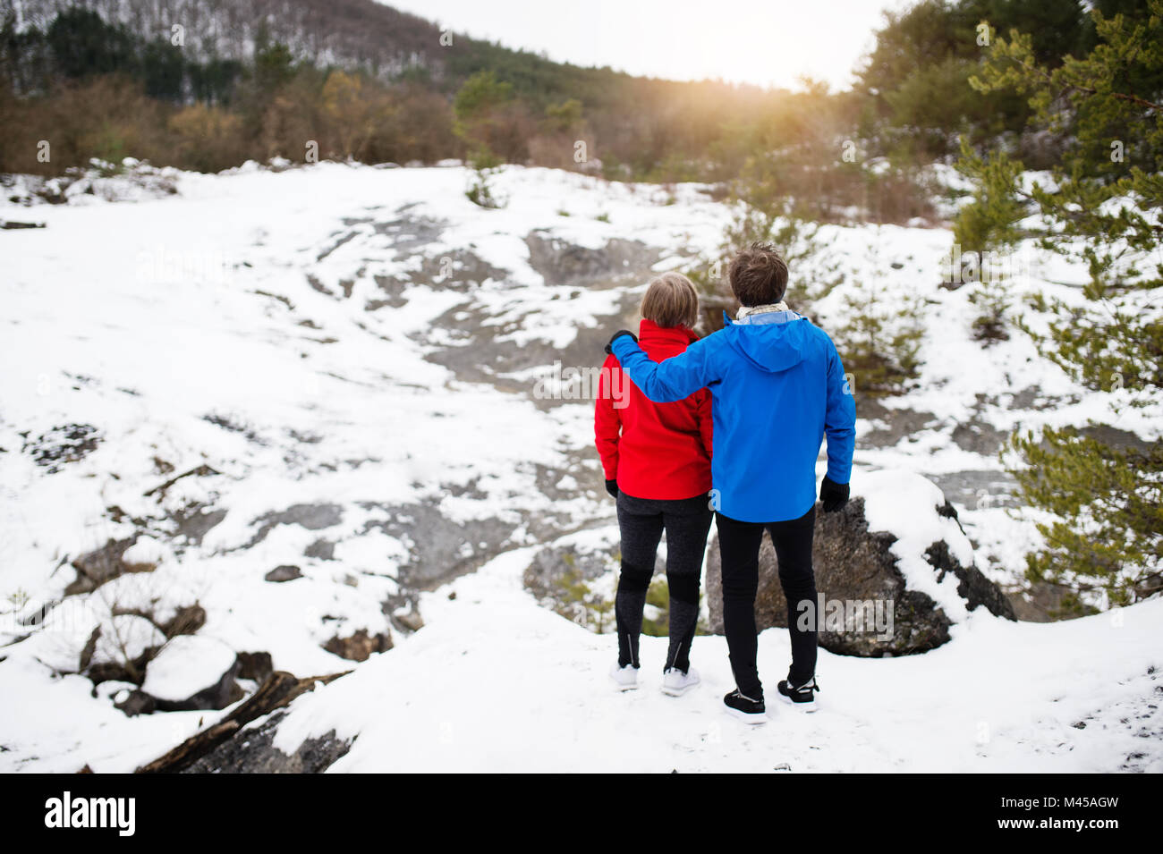 Senior couple jogging in winter nature. - Stock Image
