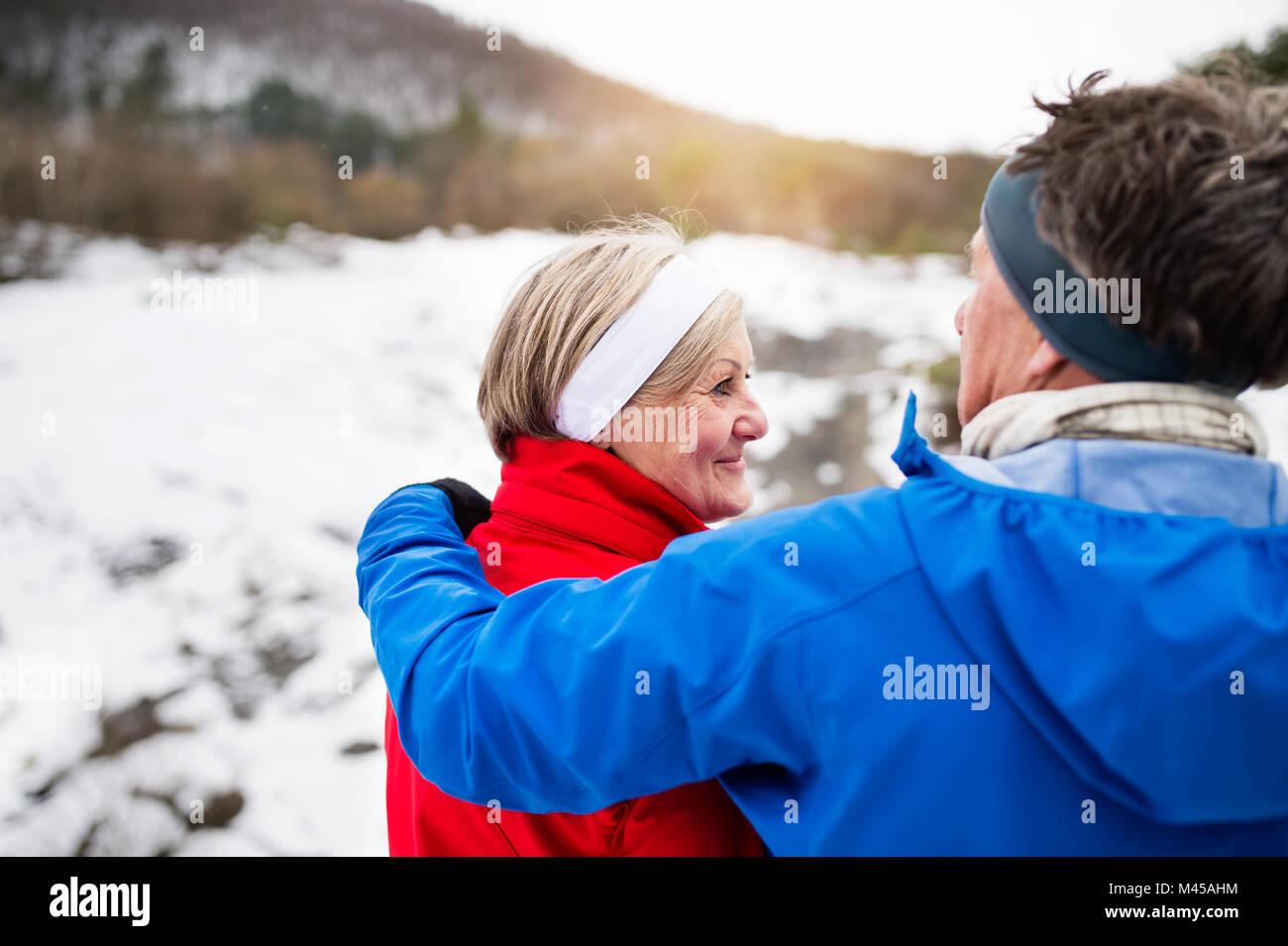 Senior couple jogging in winter nature. - Stock Image