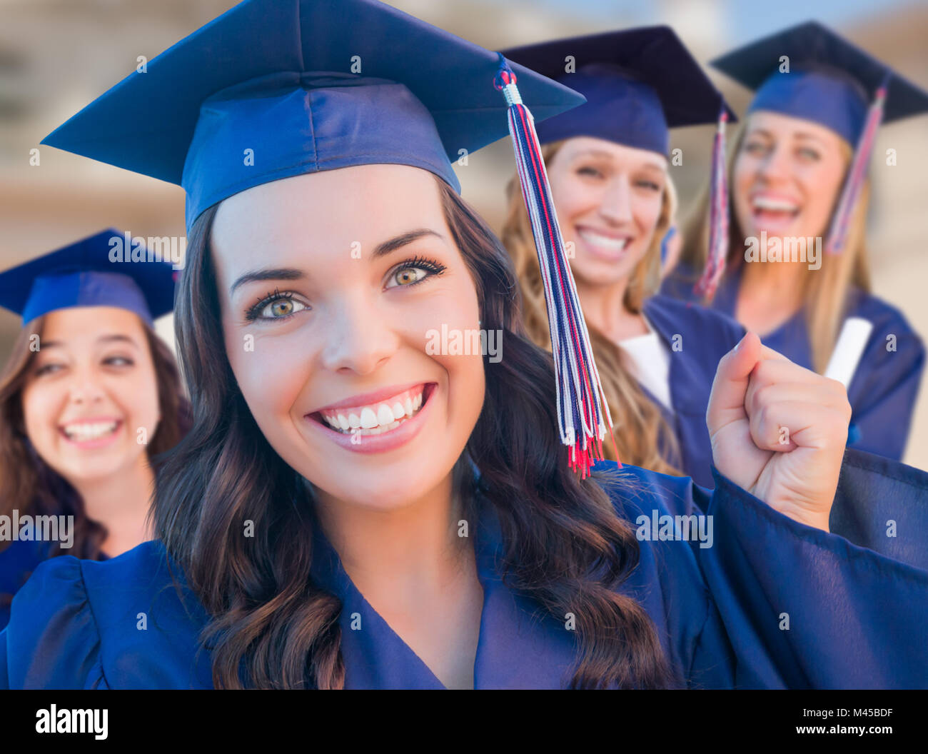Happy Graduating Group of Girls In Cap and Gown Celebrating on Campus. - Stock Image