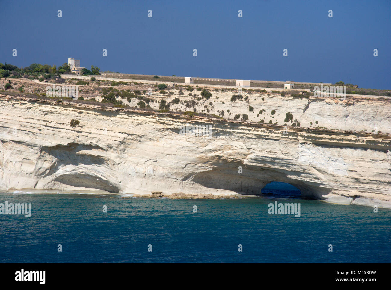 White cliffs with tunnels and caves on the east coast of Malta. - Stock Image