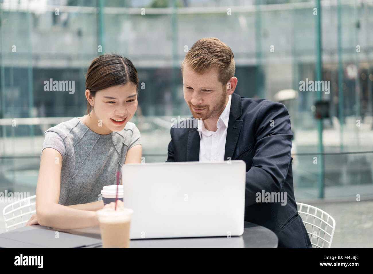 Young businessman and woman looking at laptop at sidewalk cafe meeting Stock Photo