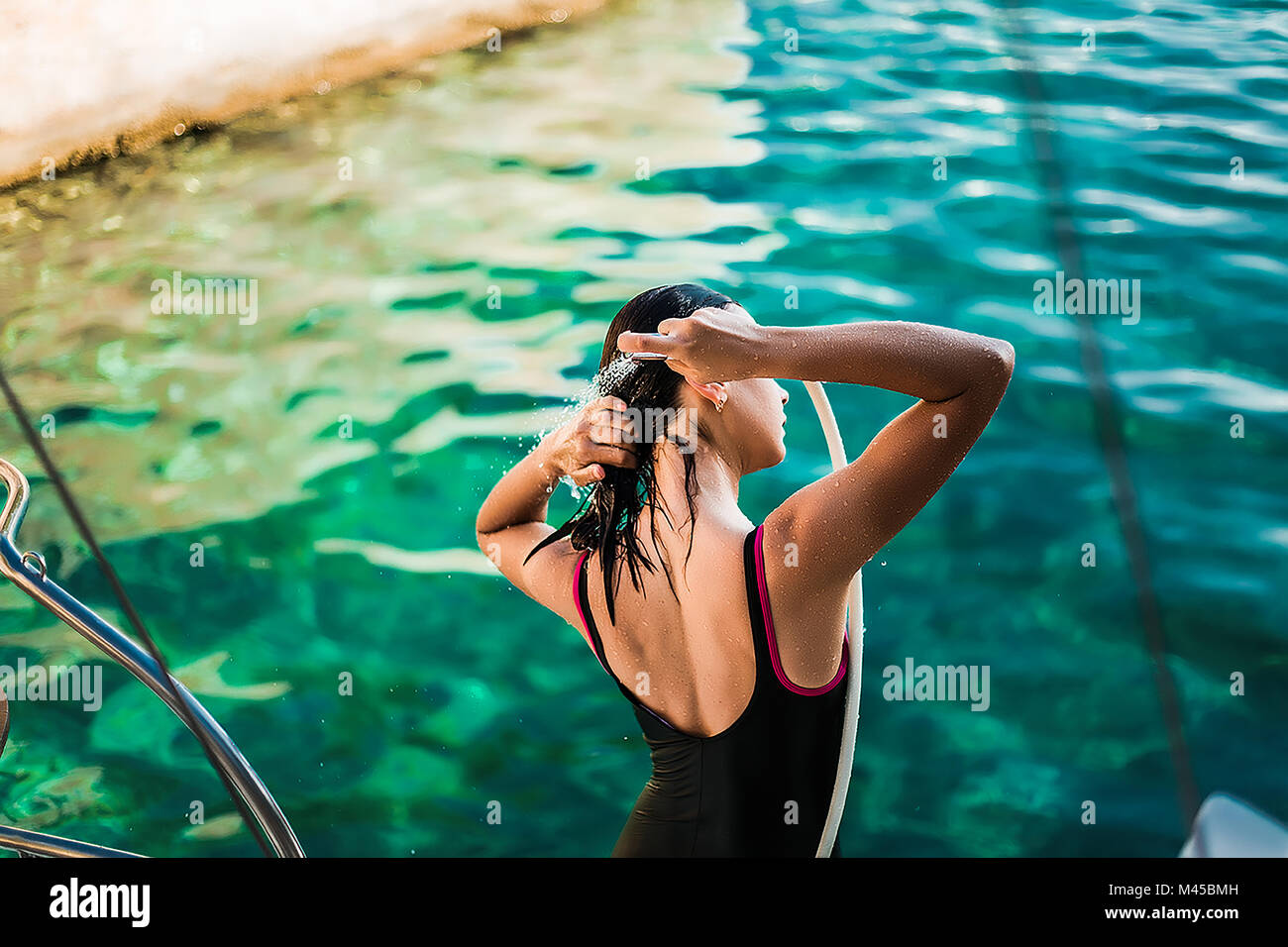 Young woman in bathing costume showering aboard yacht, Croatia - Stock Image