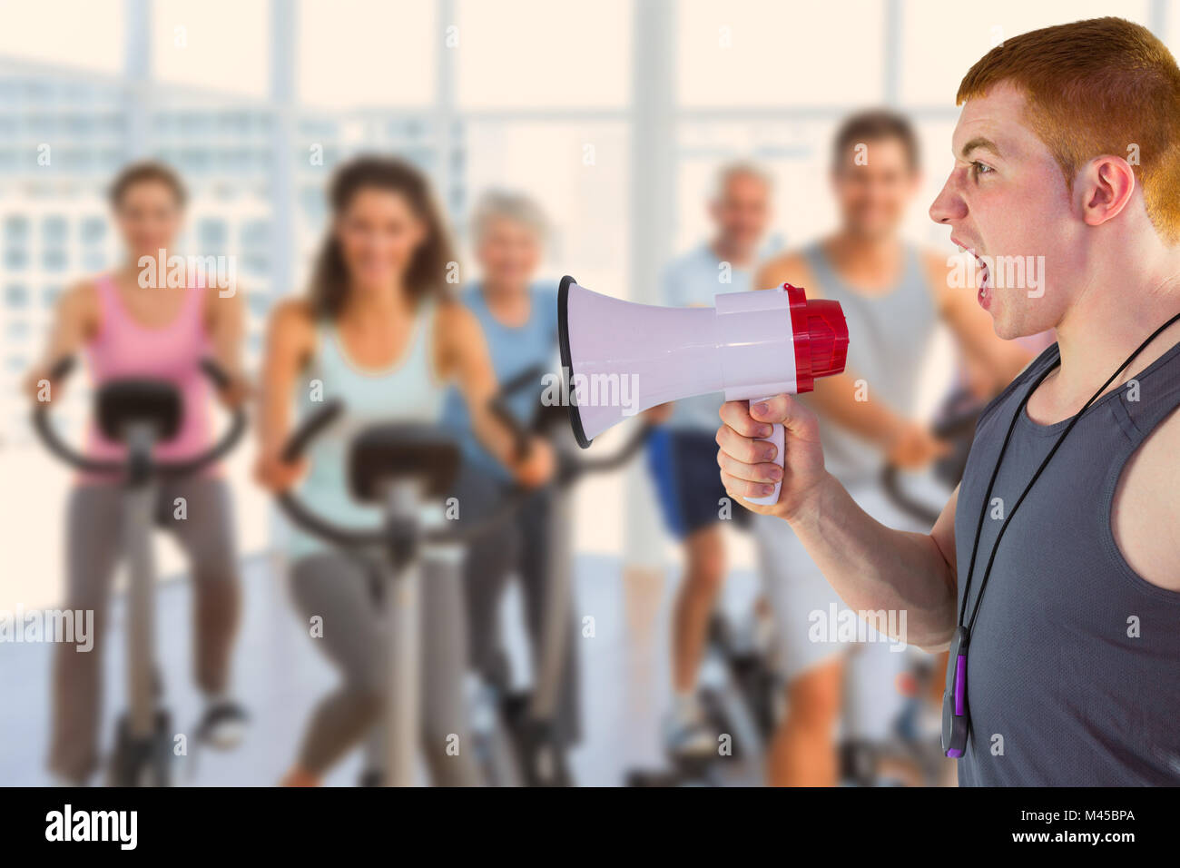 Composite image of angry personal trainer yelling through megaphone - Stock Image