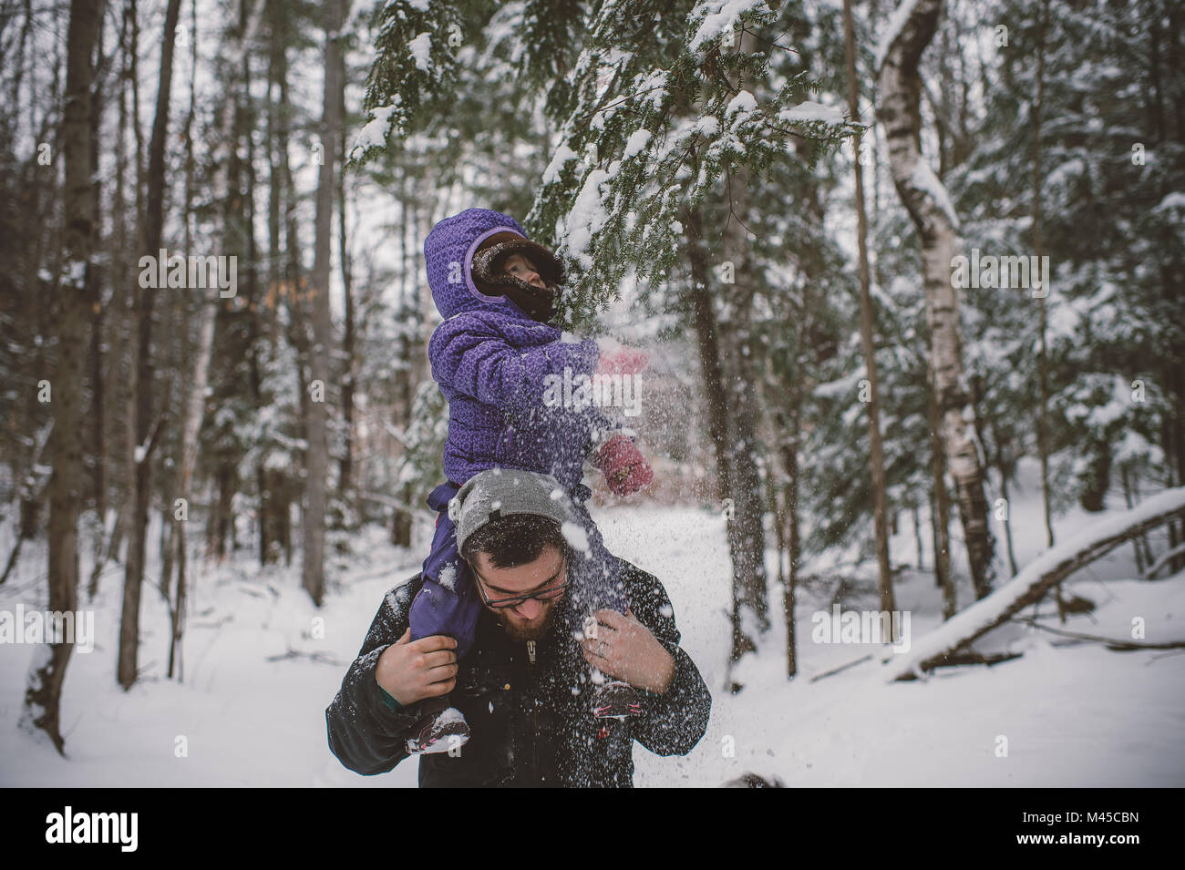 Father and daughter in snowy landscape, father carrying daughter on shoulders - Stock Image