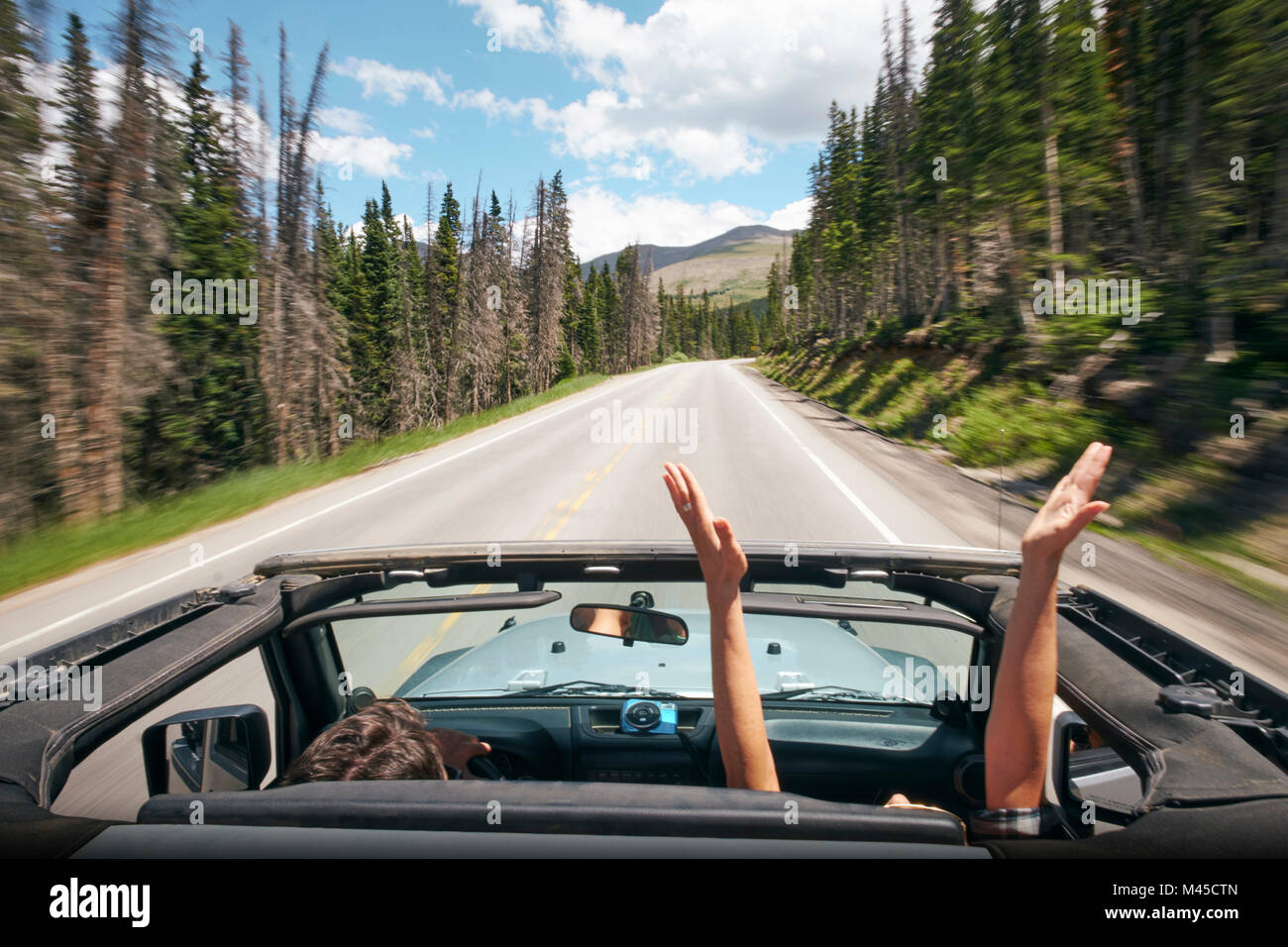 Road trip couple driving convertible on rural highway with hands raised, Breckenridge, Colorado, USA - Stock Image