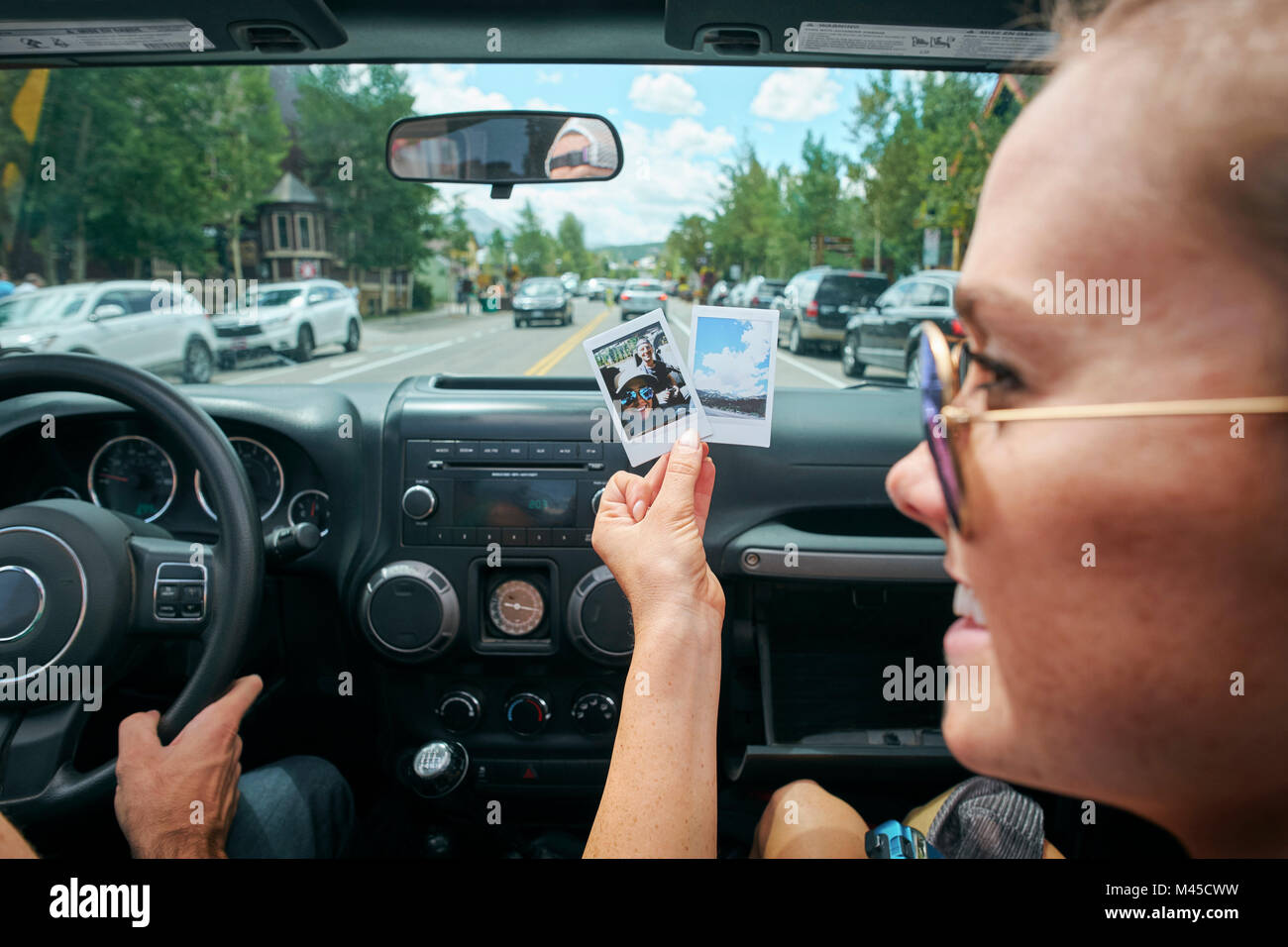 Close up of young woman on road trip holding instant photograph, Breckenridge, Colorado, USA - Stock Image