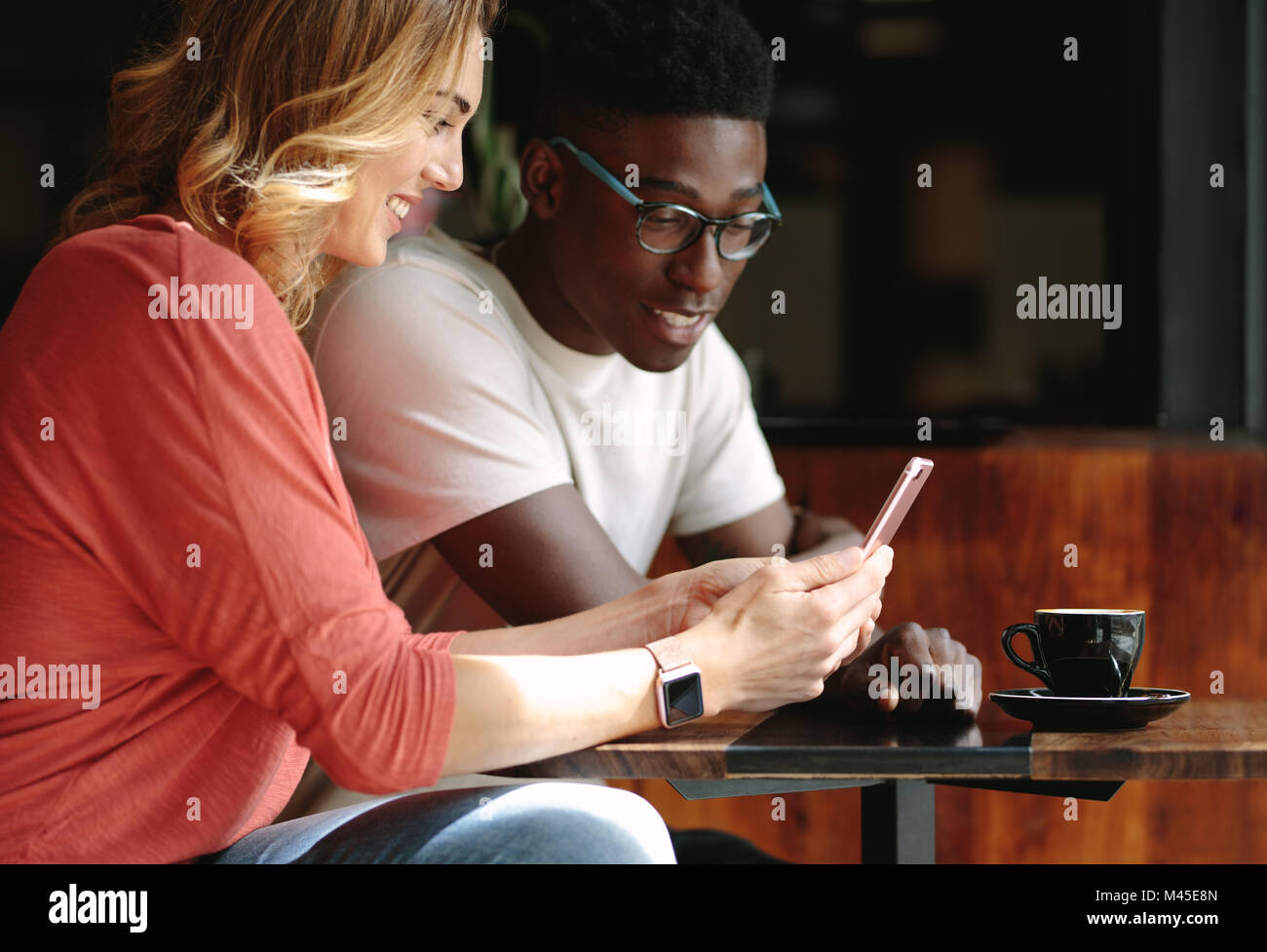 Couple sitting at a coffee shop using mobile phone. Man and woman sitting at a coffee table looking at a mobile - Stock Image