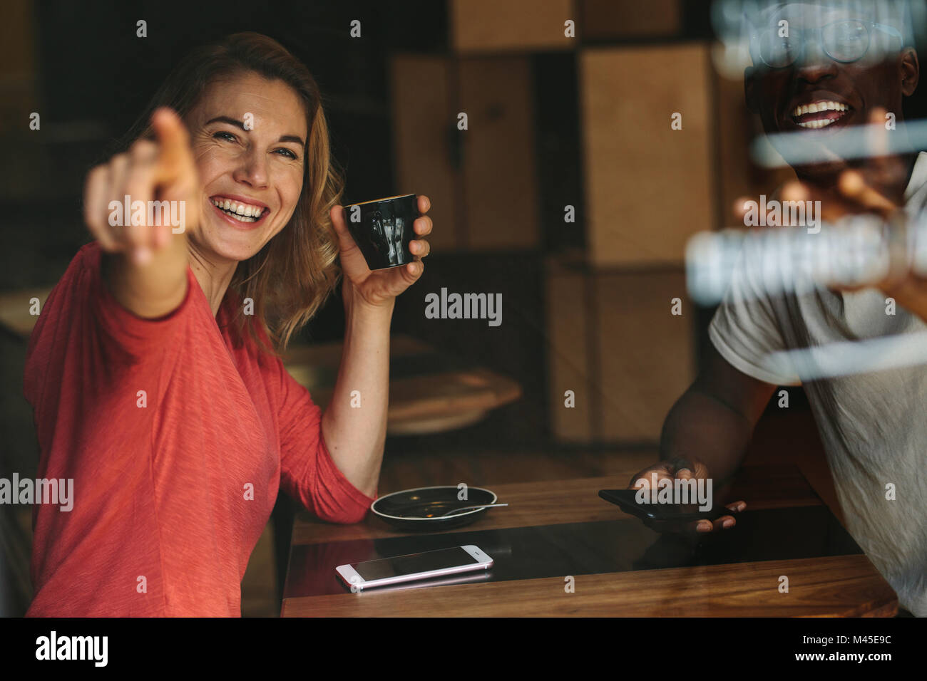 Smiling woman pointing at something sitting at a coffee table holding a coffee cup. Smiling woman sitting with her - Stock Image