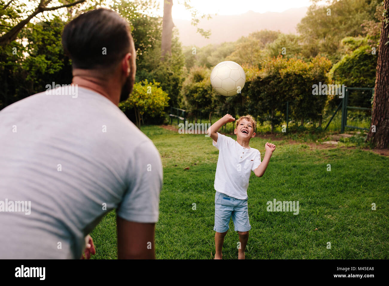 Father and son playing with a football in backyard garden. Happy little boy passing ball to his father. - Stock Image