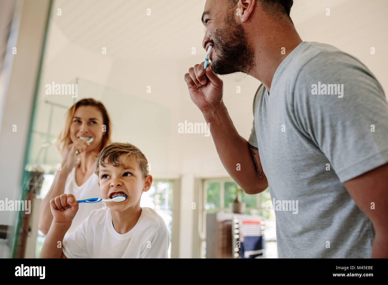 Cute little boy brushing teeth with his father and mother in bathroom. Young family brushing teeth together in bathroom. - Stock Image