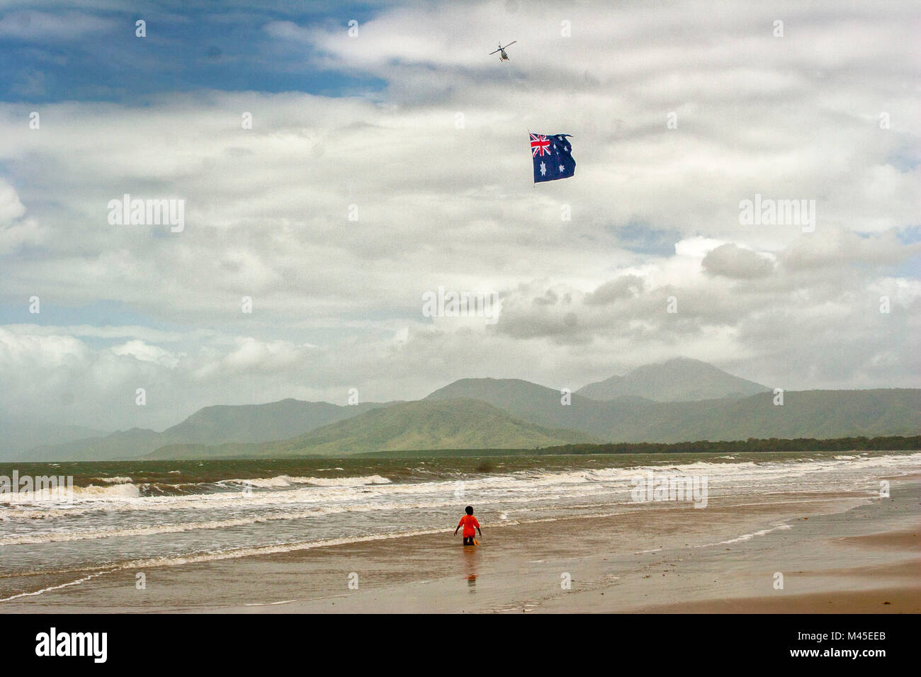 Lone person on Port Douglas beach (North Queensland, Australia) with Australian flag towed by helicopter above Stock Photo