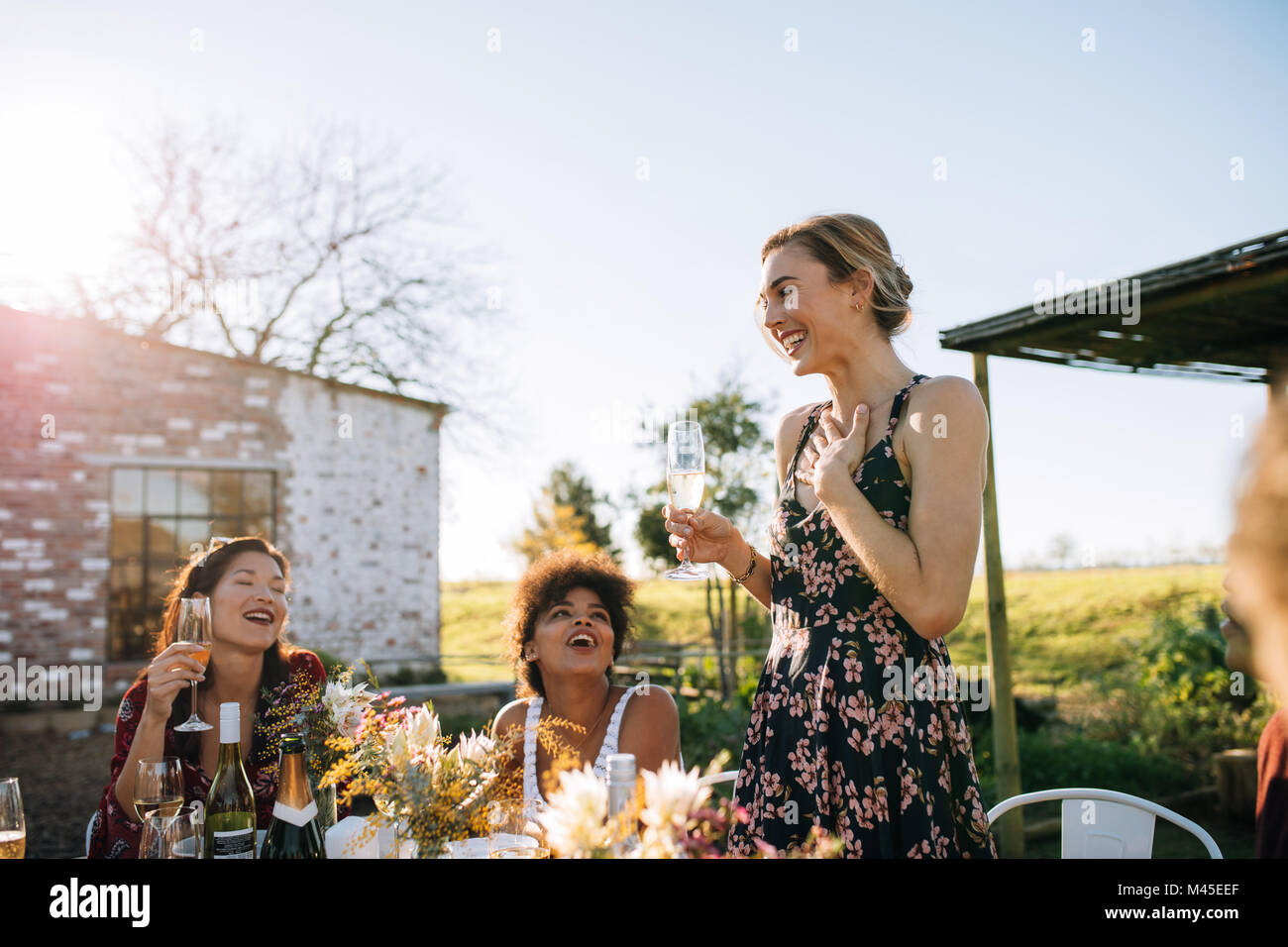 Overwhelmed woman sharing good news with friends at garden restaurant. Friends celebrating a special occasion at - Stock Image