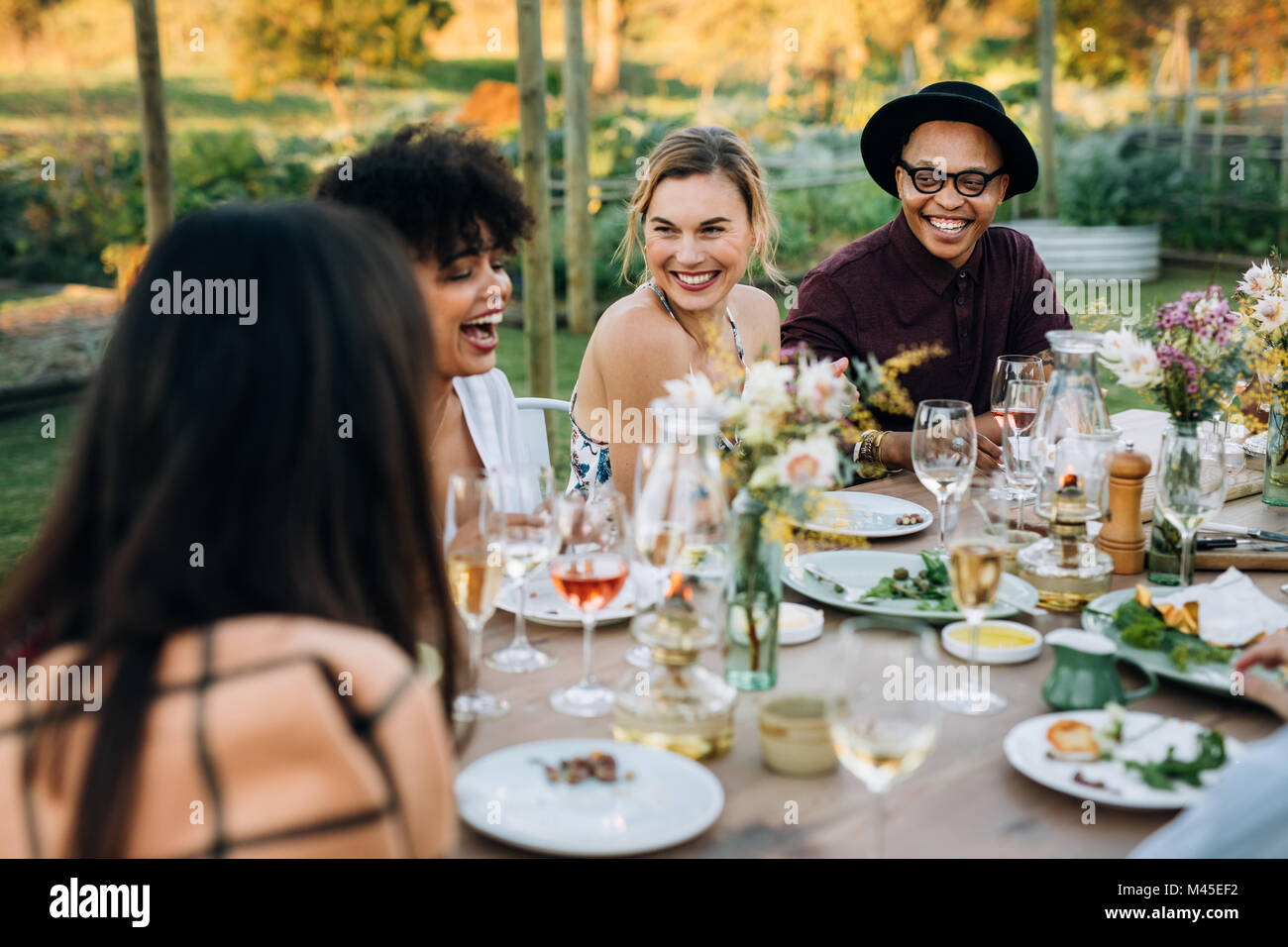 Group of friends enjoying outdoor party in home garden. Millennials  enjoying summer meal at restaurant. - Stock Image