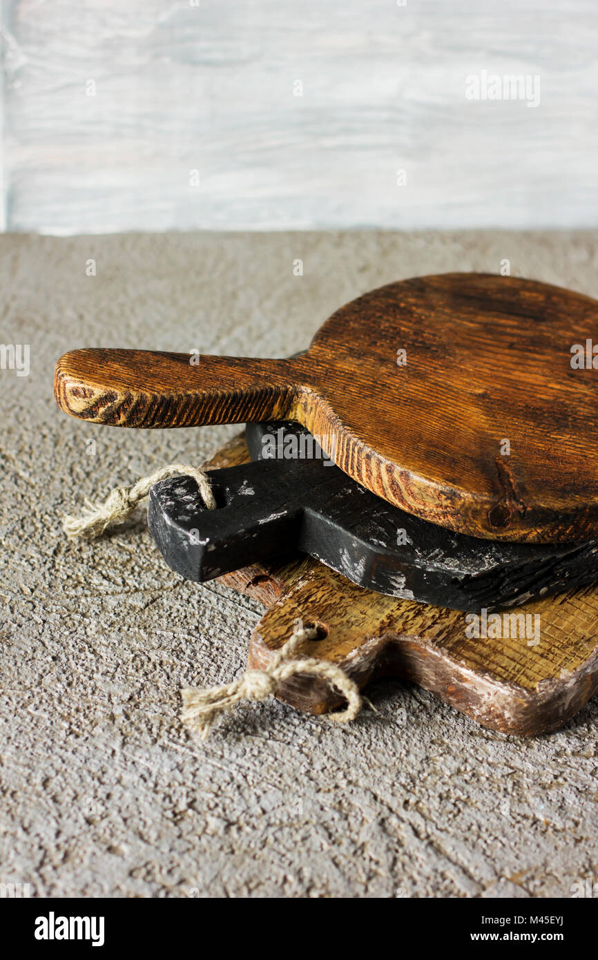 Wooden cutting boards on grey concrete background. Props for food photography - Stock Image