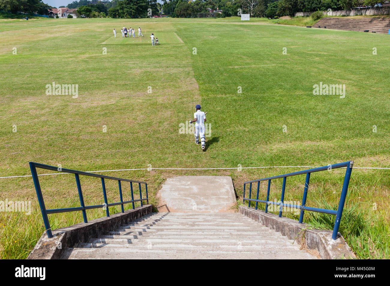 Cricket game high schools teenagers new batsman from steps above playing field. - Stock Image