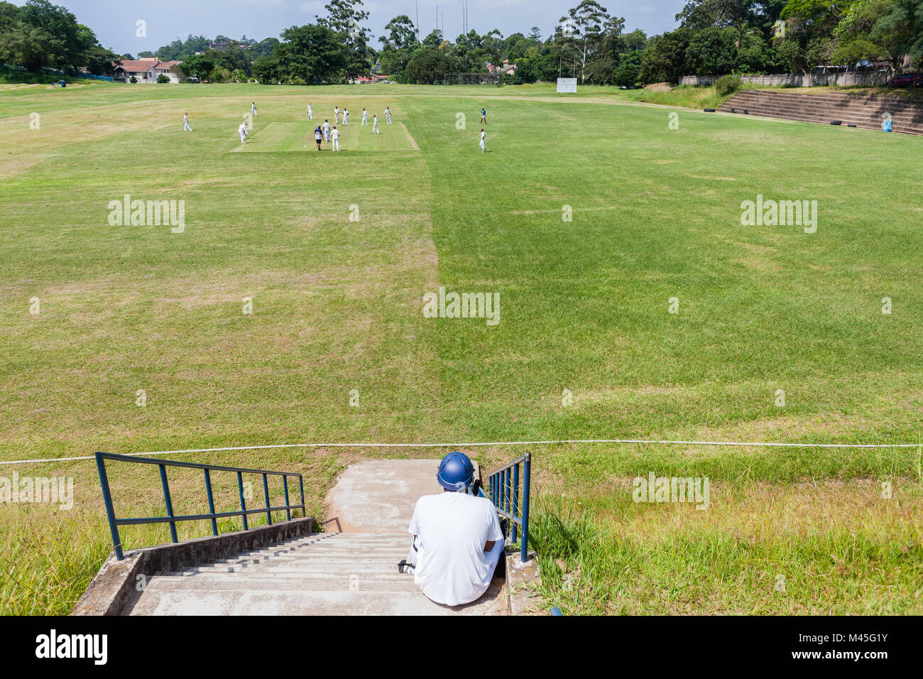 Cricket game high schools teenagers batsman waits on steps above playing field. - Stock Image