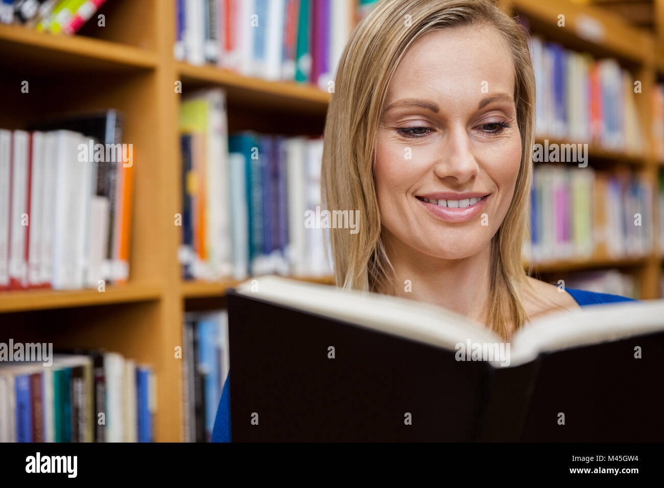 Happy female student reading a book in the library - Stock Image