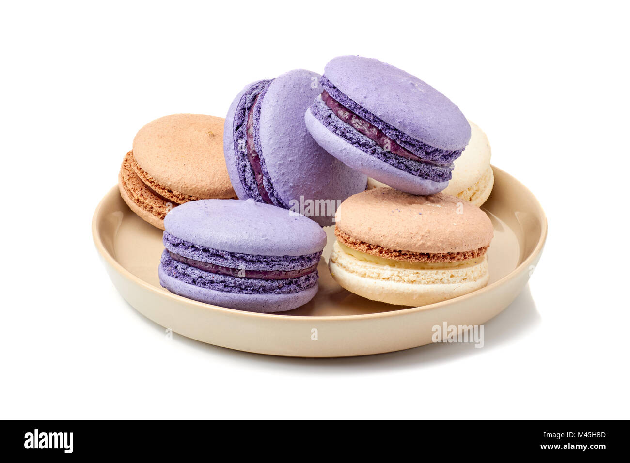 Plate vith violet and beige macarons on white - Stock Image