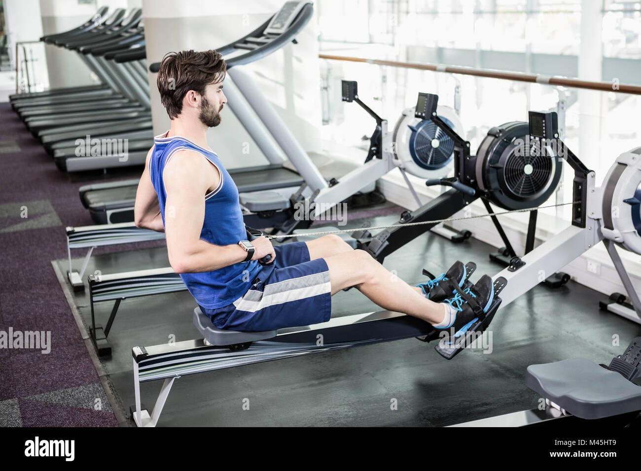 Handsome man doing exercise on drawing machine - Stock Image