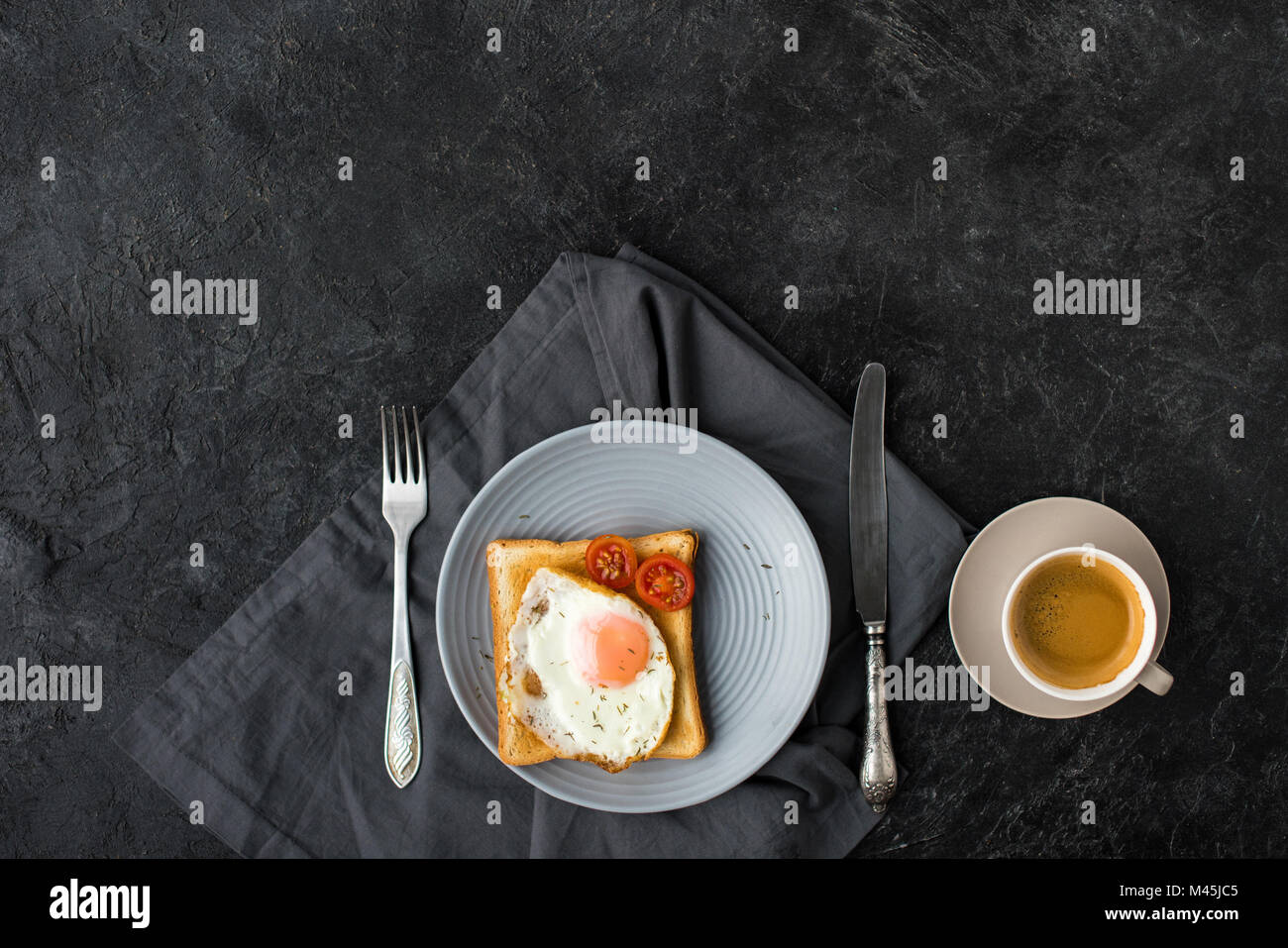 flat lay with cup of coffee and toast with fried egg and cherry tomatoes for breakfast on dark surface - Stock Image