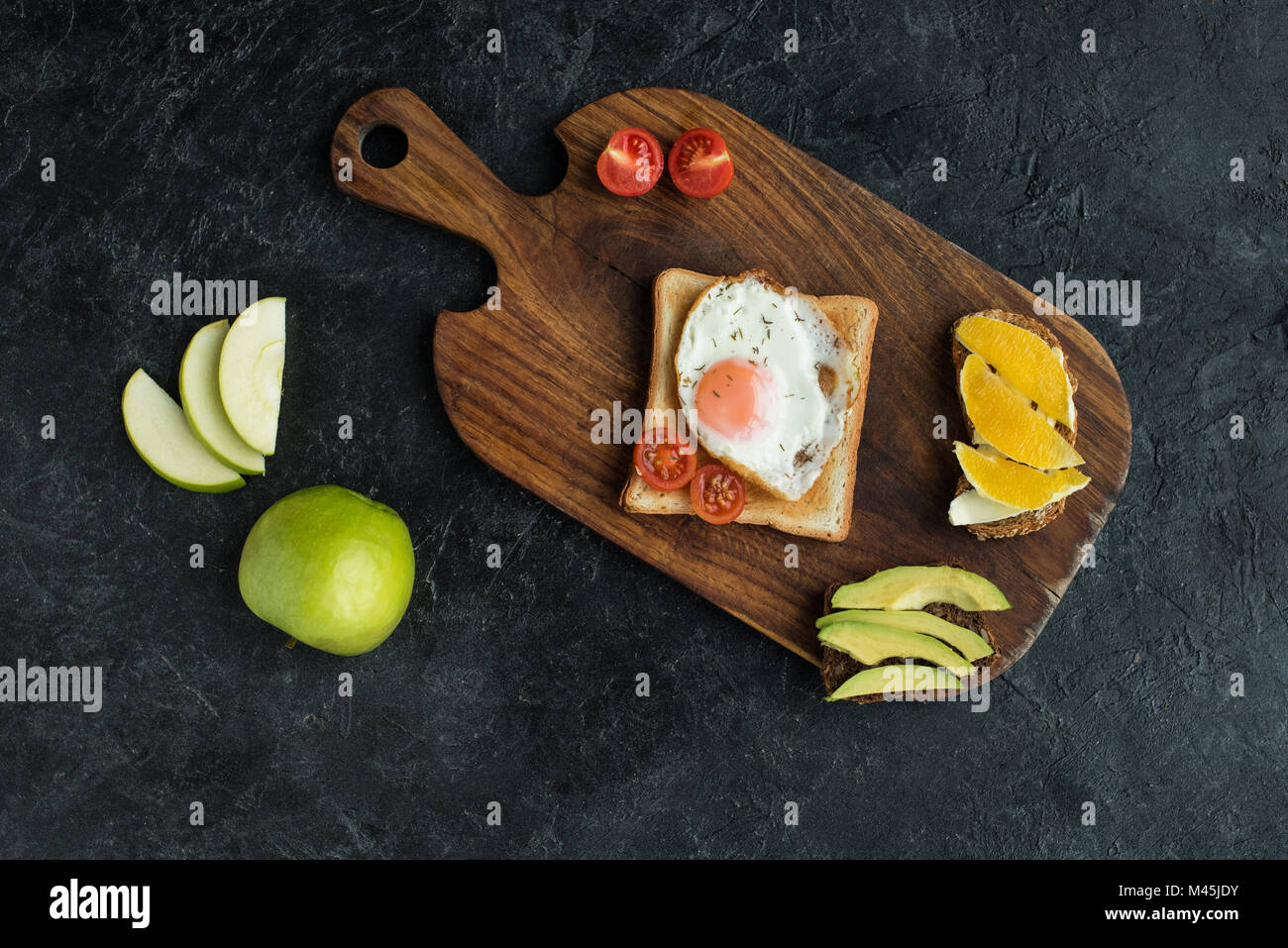 top view of toast with fried egg and cherry tomatoes for breakfast on cutting board - Stock Image