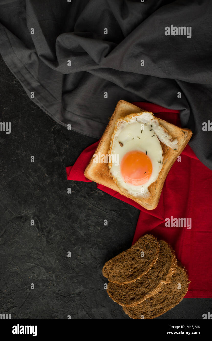 top view of fried egg on toast and slices of bread on dark surface - Stock Image