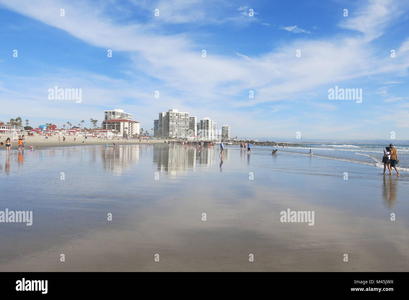View of Coronado Beach on a sunny spring day, with the water reflecting a big sky Stock Photo