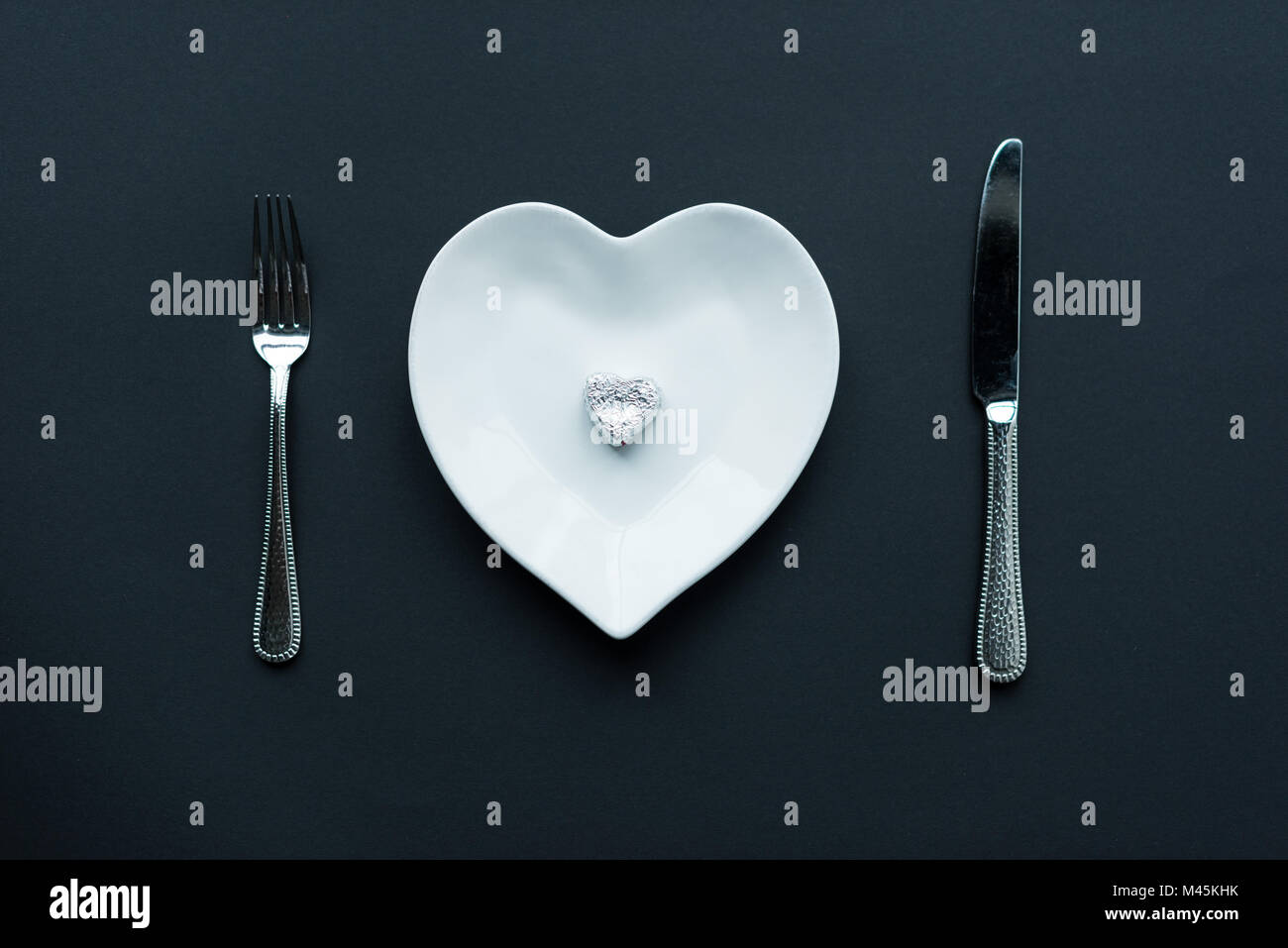 Top view of wrapped candy on white heart shaped plate with cutlery