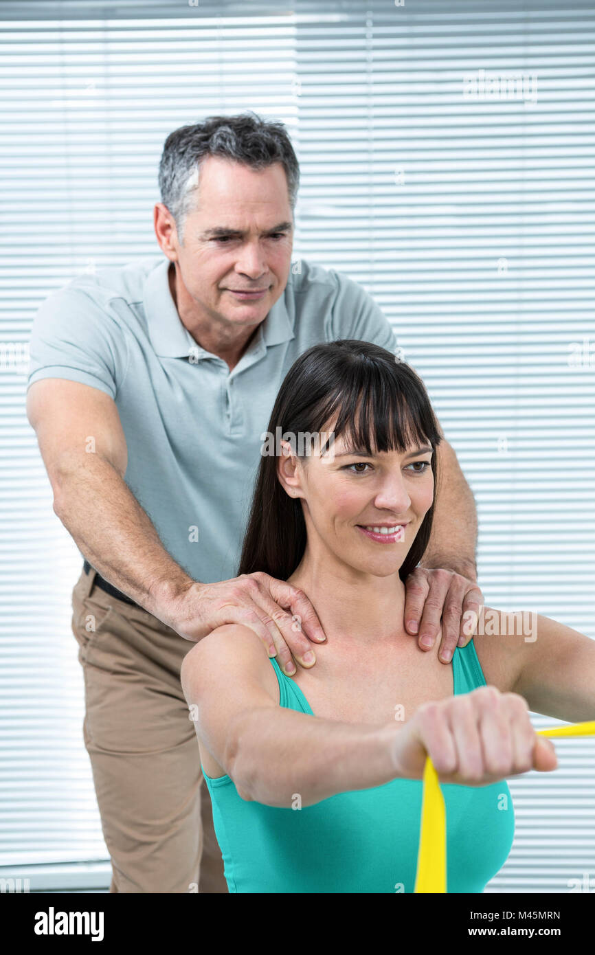 Physiotherapist guiding pregnant woman with exercise - Stock Image