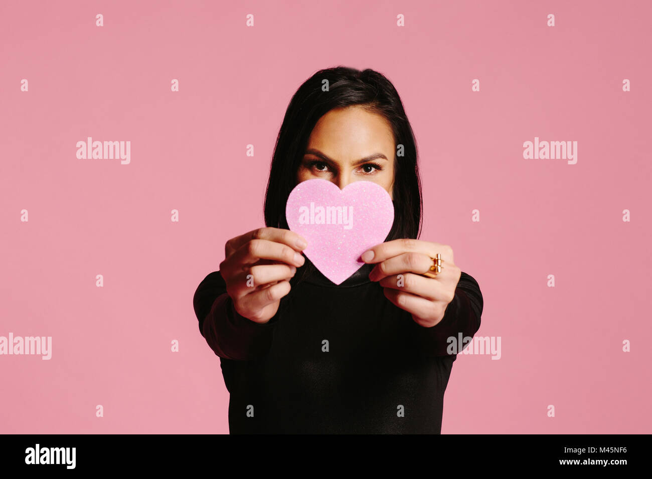 Woman in black showing pink heart covering half her face, be my valentine - Stock Image