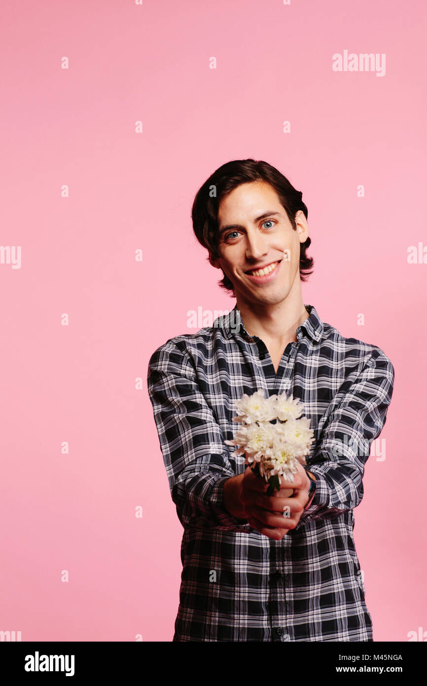 Sweet guy in checkered shirt holding and offering bouquet of white flowers - Stock Image