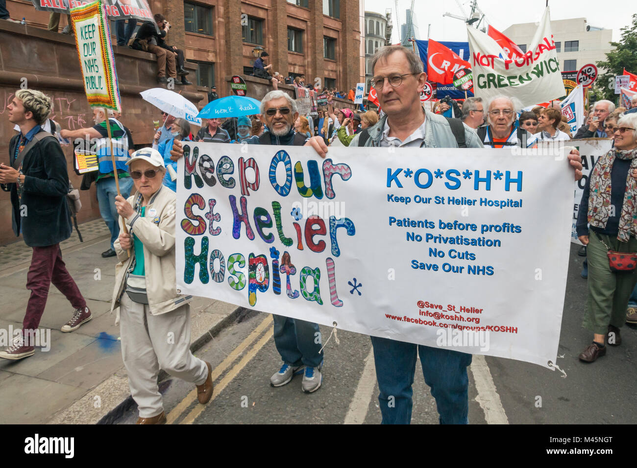 A woman carries an embroidered placard 'Keep Our NHS PUblic' next to the Keep of St Helier Hospital banner - Stock Image