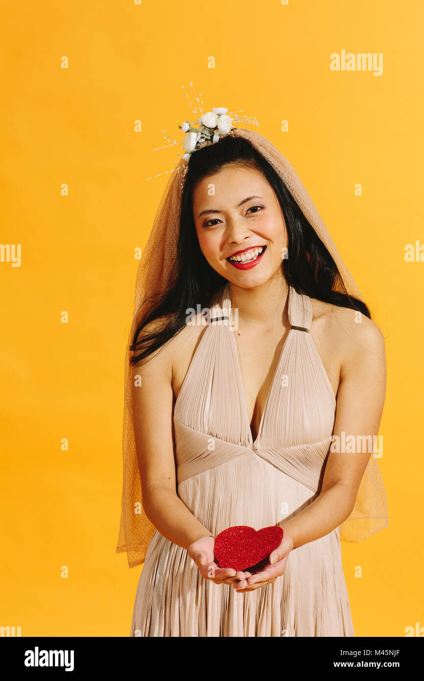 Smiling Asian bride holding a red heart looking at camera - Stock Image
