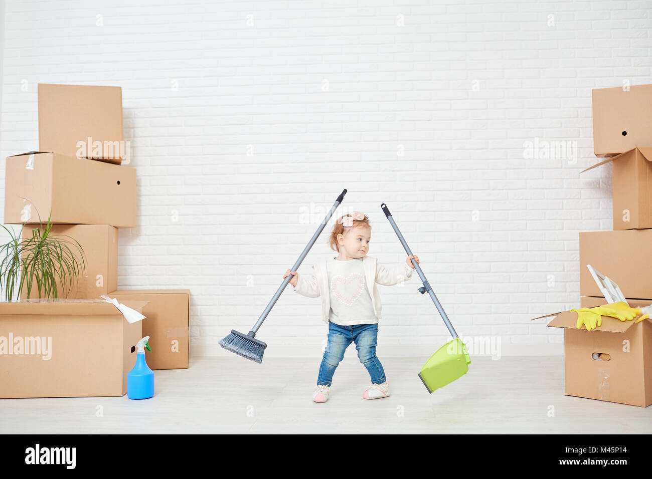A funny child does the cleaning in the house Stock Photo