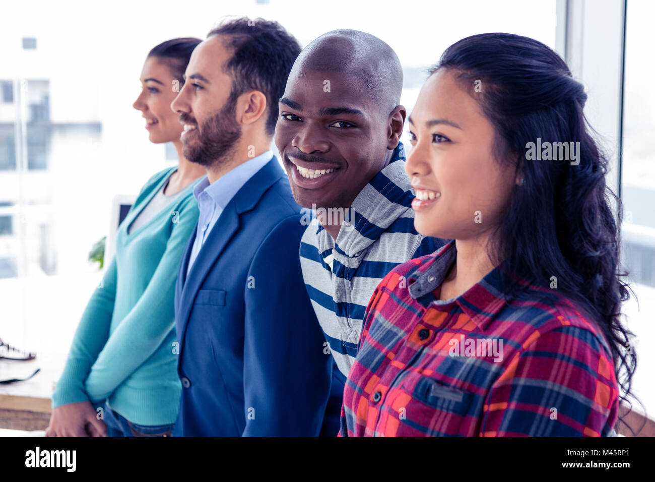 Portrait of cheerful businessman with colleagues - Stock Image