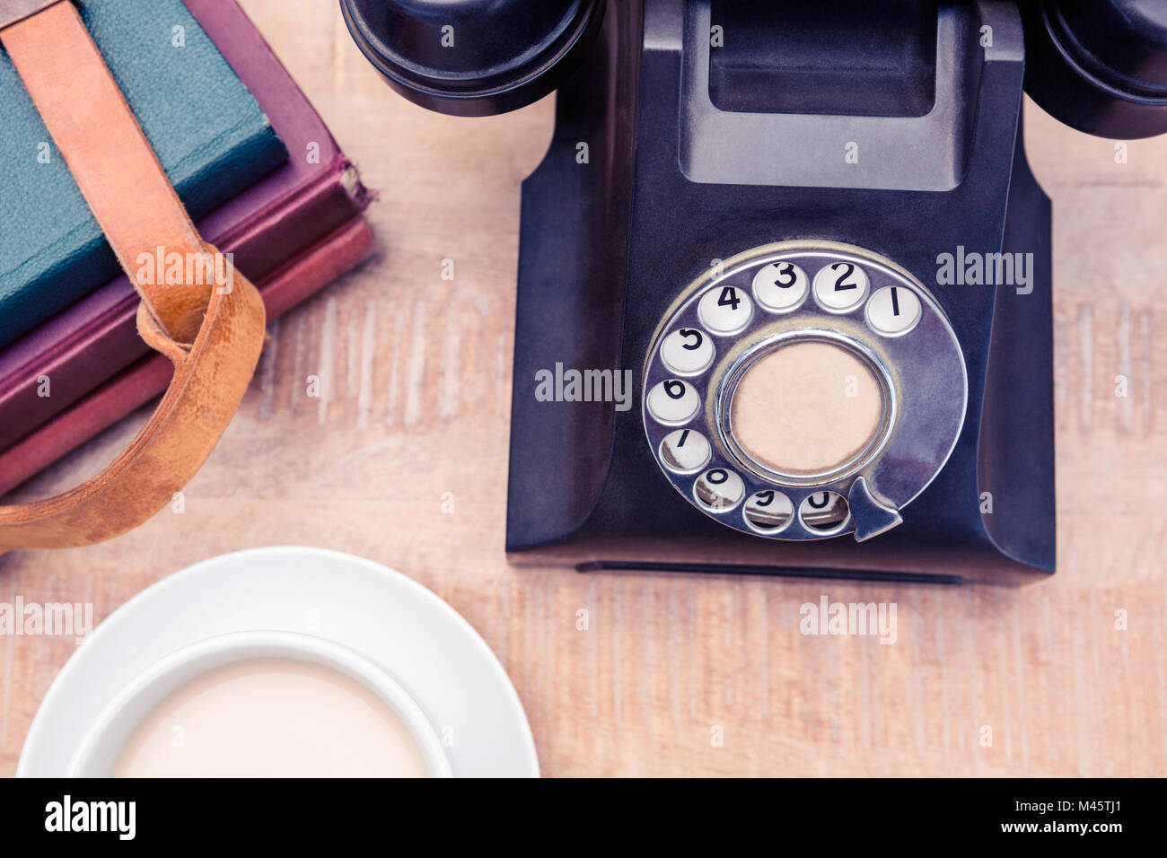 Old landline telephone with diaries and coffee - Stock Image